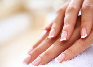 Closeup of nicely manicured female fingernails. One hand is placed on top of other, both on a white towel. Very nice french manicure with transparent nail paint. Blurry beige background. Copy space.