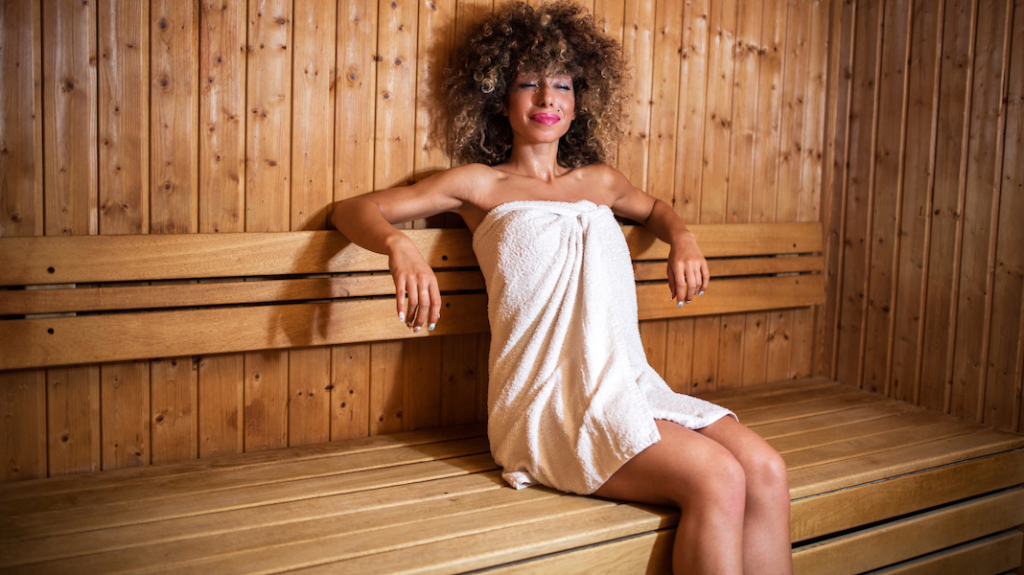 Smiling African American woman relaxing in sauna.